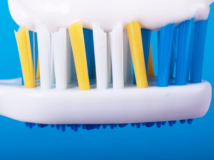 close up of colgate toothpaste on toothbrush