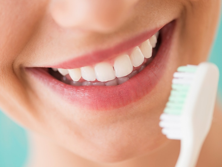 close up of smiling mouth with colgate toothbrush