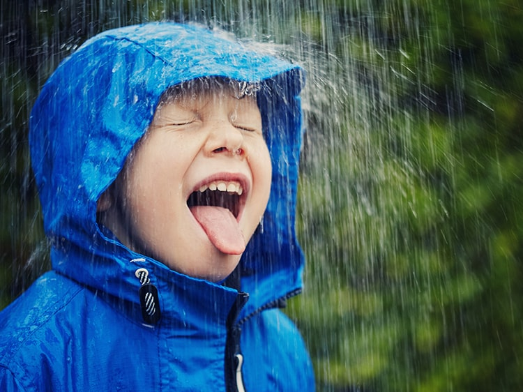 A kid with open mouth in the rain