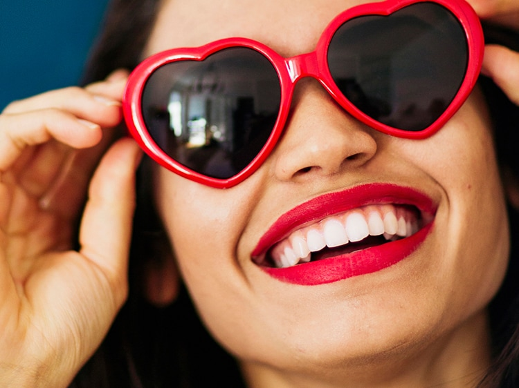 woman wearing heart shaped sunglasses showing white teeth