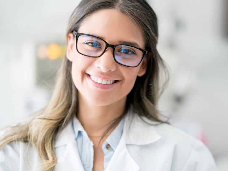 smiling woman wearing glasses showing white teeth
