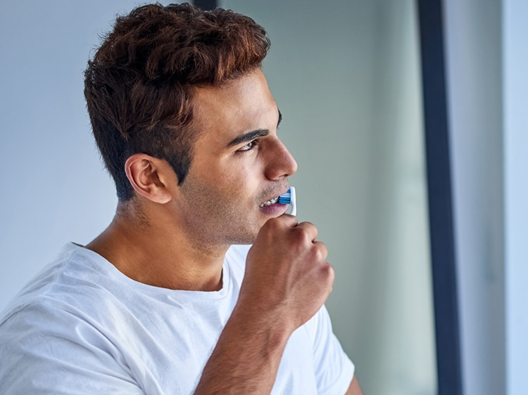 man brushing his teeth with colgate toothbrush