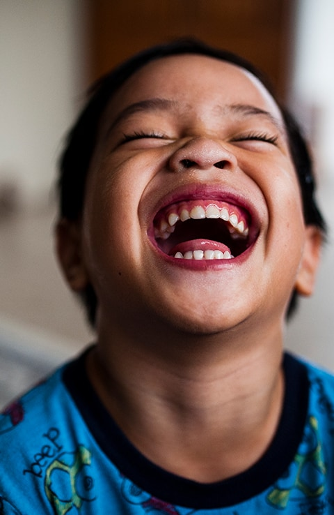 Young boy laughing in home