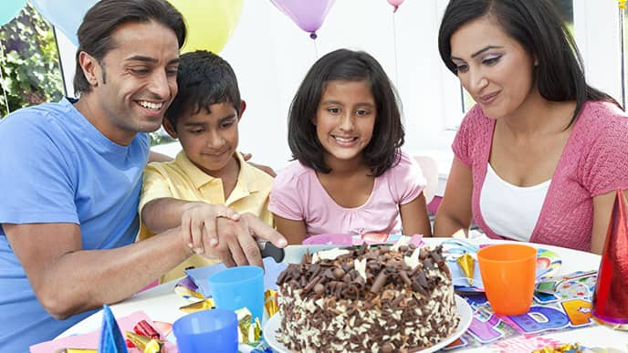 Family eating a large piece of cake together
