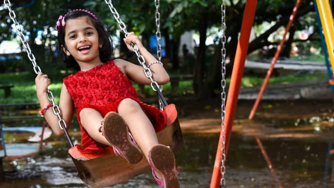 Little girl swinging in the park