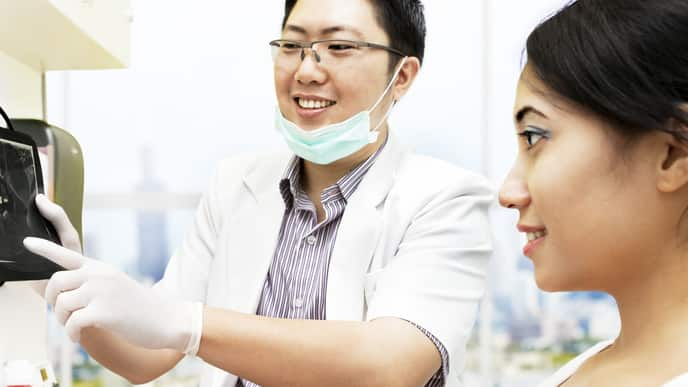 Dentist explaining a method of wisdom teeth pain relief