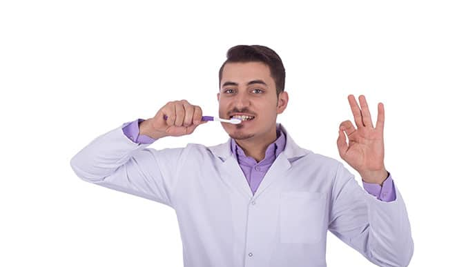 Dentist showing how to brush teeth properly