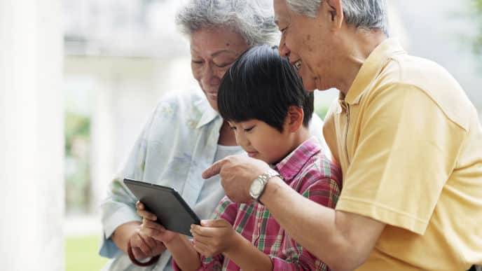 Asian grandparents with grandson using tablet