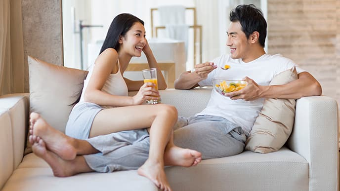 Asian couple having breakfast on couch