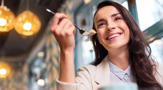 Woman smiling eating with a fork