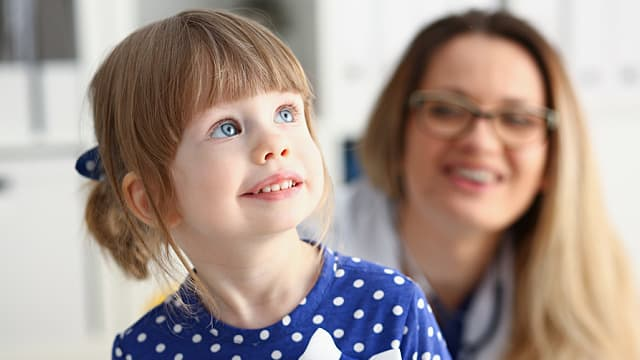 A Child Smiles in a Dentist's Office Awaiting a Routine Oral Exam