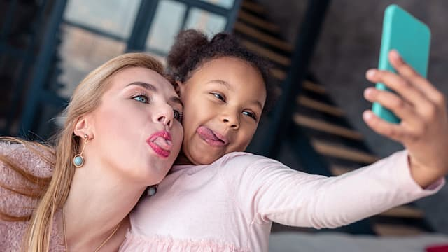 A Woman and Little Girl Sticking Out Their Tongues