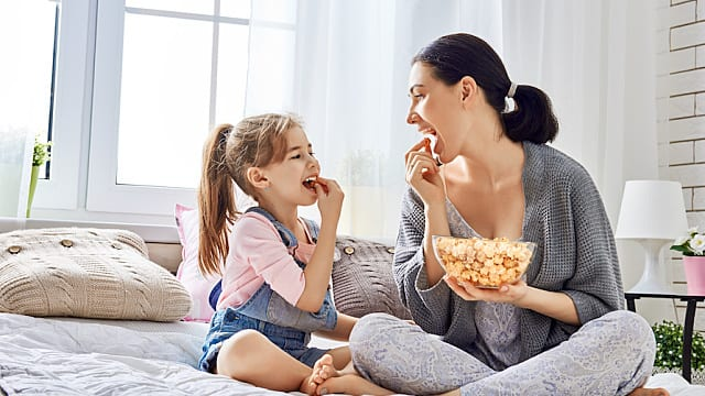 Mother and daughter eating popcorn in bed.
