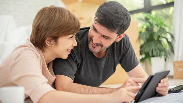 Couple with digital tablet and blueprints planning their new moving house.
