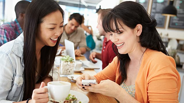 Two Women Chat and Eat in a Cafe