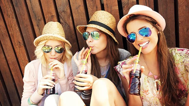 Three young women are drinking soda