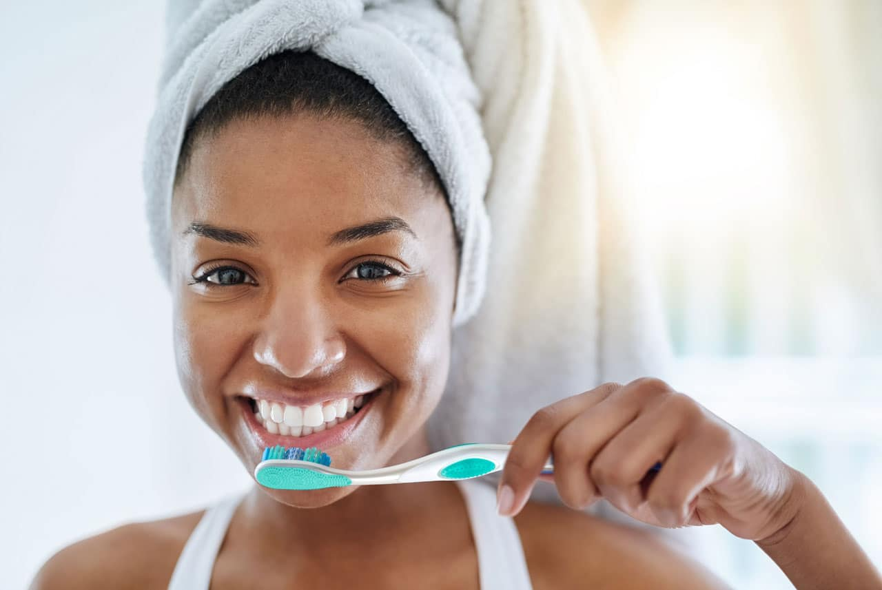 Young girl smiling while holding her toothbrush ready to brush her teeth