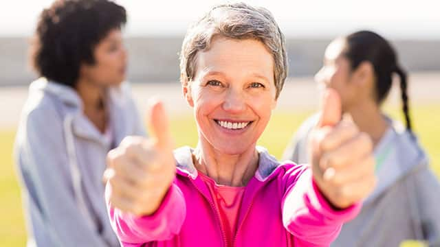 grey-haired woman in pink sweatshirt holding thumbs up