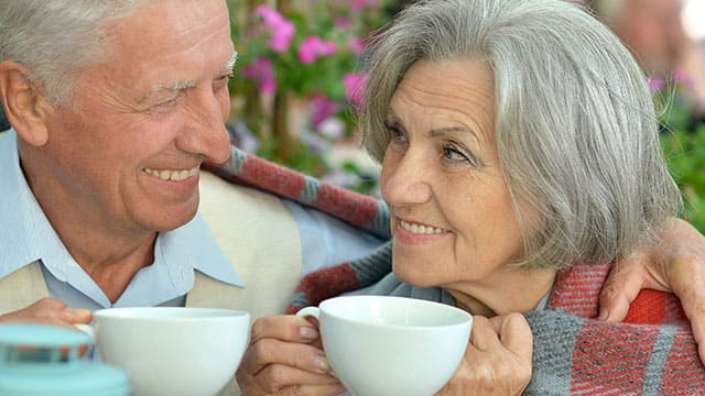 Elderly couple holding a cup of coffee as they snuggle with a blanket wrapped around them