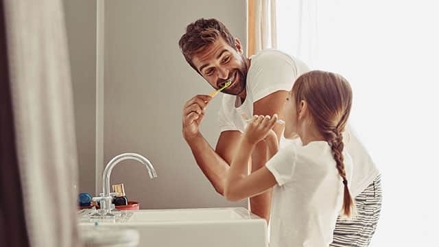Father and daughter are brushing their teeth over the sink