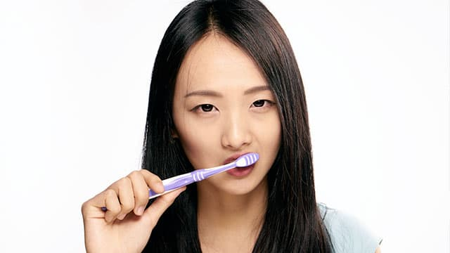Asian woman is brushing her teeth