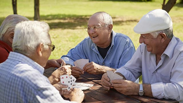 a group of old male is playing cards and talking about HPV in men