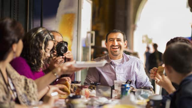 man is happy for eating with his family in a restaurant