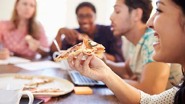 Friends eating pizza together happily