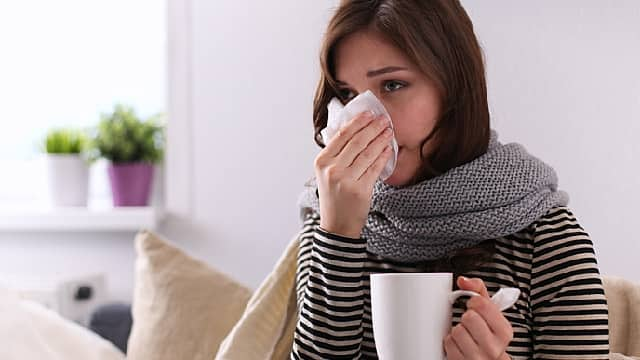 Girl suffering of cold and having stuffy nose