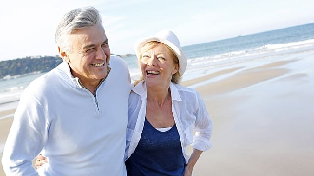 a senior couple are walking along the beach after TMJ treatment