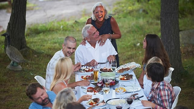 a family is eating together happily after gingival hyperplasia treatment