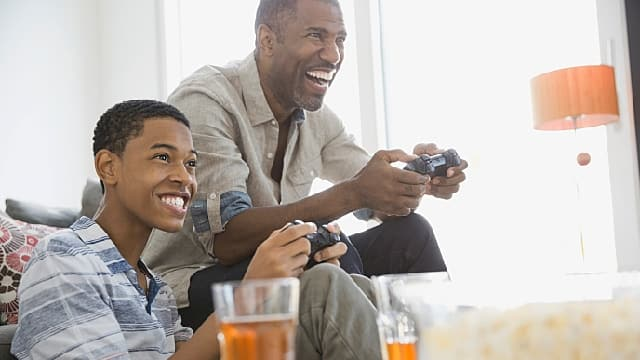 Father and son playing video games together at home