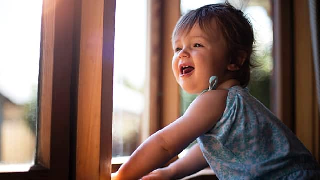 baby looking out window with smile