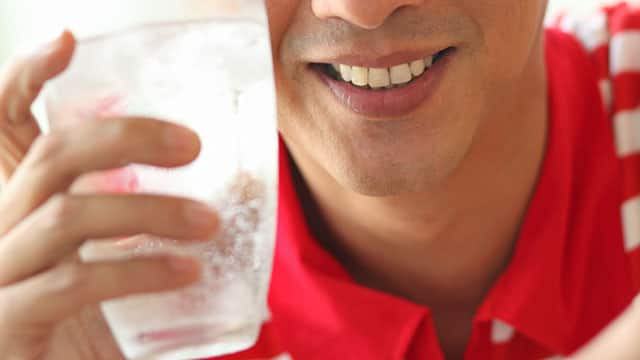 A close up of the man holding a glass with sparkling water and ice