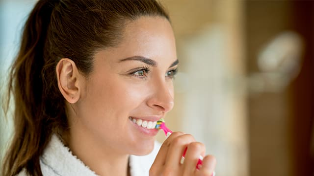 Brown hair woman in a white robe, happily brushing her teeth.