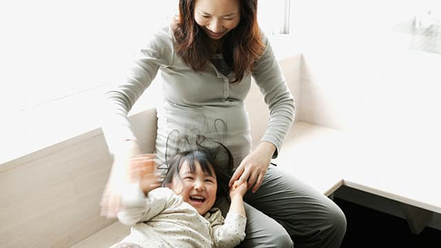a pregnant mother is playing with her daughter after taking care of bleeding gums