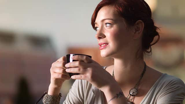 A woman is drinking coffee in a cafe