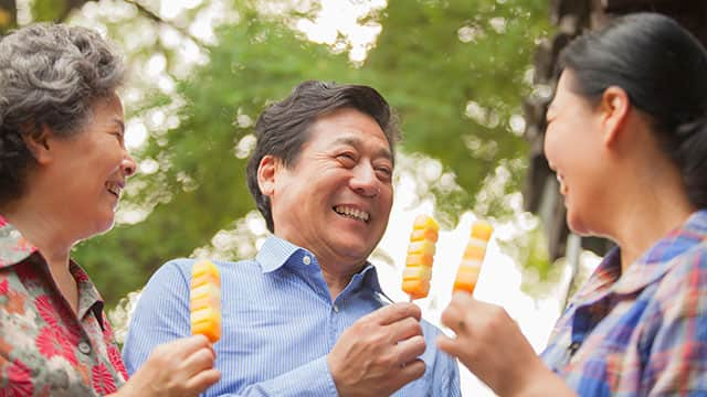 Chinese family of three smiling and eating ice cream