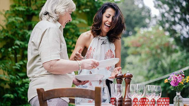 An older and a younger women preparing table outdoors