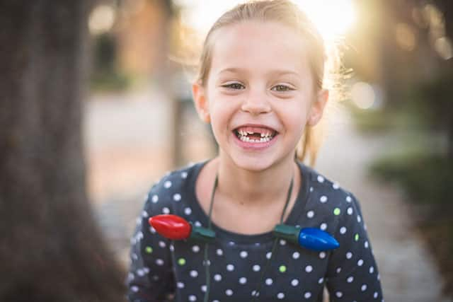A small girl has a missing front tooth and smiling outdoors