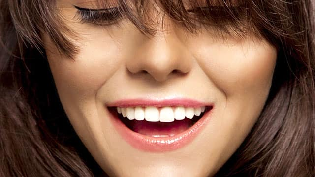 Young woman smiles showing white teeth