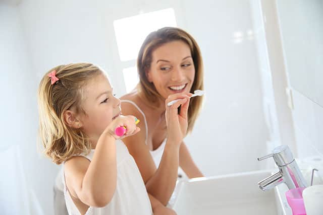 Mother and daughter are brushing teeth