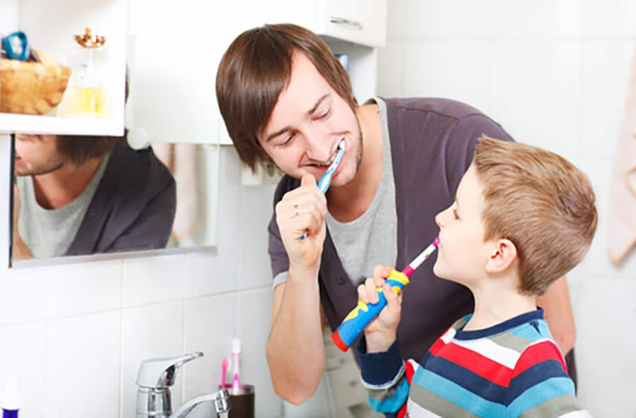 Father and son brushing their teeth in the bathroom in front of the mirror