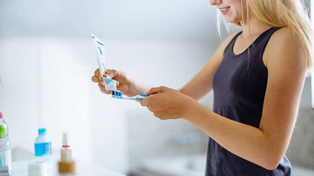 A young woman is adding a toothpaste to a toothbrush