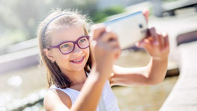 Young girl with braces and glasses smiling for a selfie