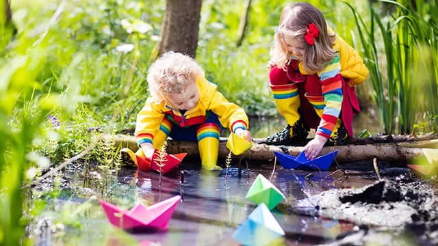 Kids playing with colorful paper boats in a park