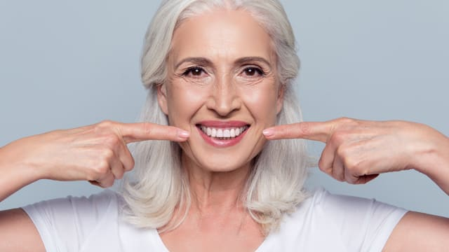 A older woman smiling and pointing to her teeth