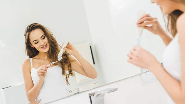 A young smiling woman applying toothpaste on a toothbrush that is in hands