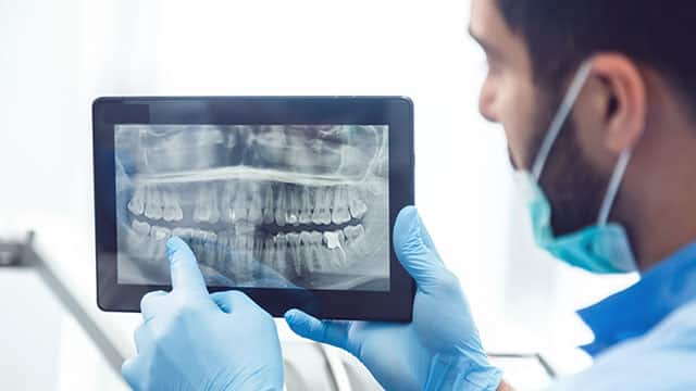 Dentist showing teeth x-ray on tablet and pointing at the screen
