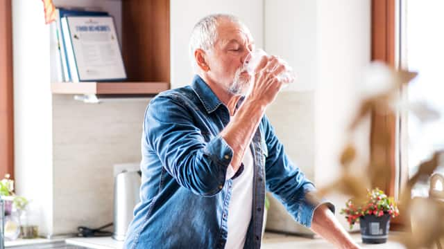 A senior man in a denim shirt drinking a glass of water in his kitchen